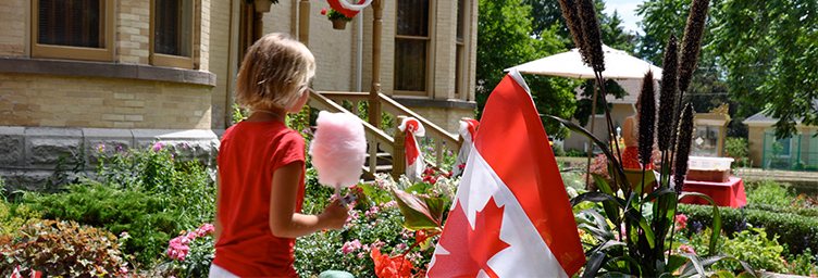 girl with cotton candy walking by Canadian flag