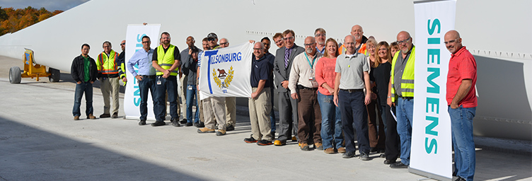 siemens employees and town officials in front of wind turbine blade