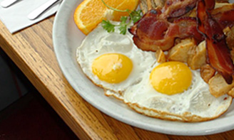 eggs and bacon, homefries and orange slices on a plate
