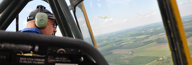 view of pilot from back seat of Harvard with another Harvard visible out window