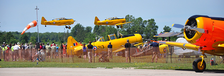 two harvards taking off with crowd underneath and third plane in foreground
