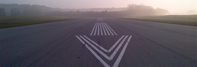 runway markings with sunrise and mist