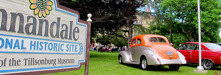 vintage cars on lawn next to Annandale House sign