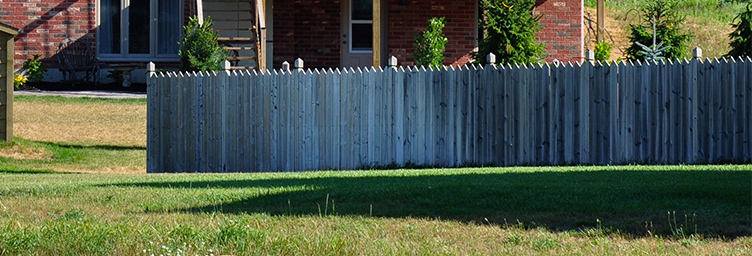 fence in backyard with house in behind