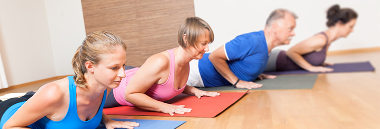 adults doing yoga on mats