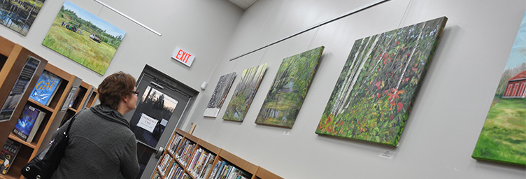 woman looking at art on walls in Tillsonburg Library