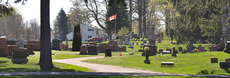 Tillsonburg Cemetery showing stones with Canadian flag in background