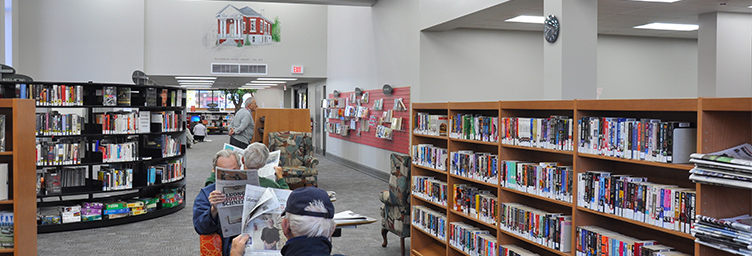 Interior of Tillsonburg Library showing stacks and patrons reading papers
