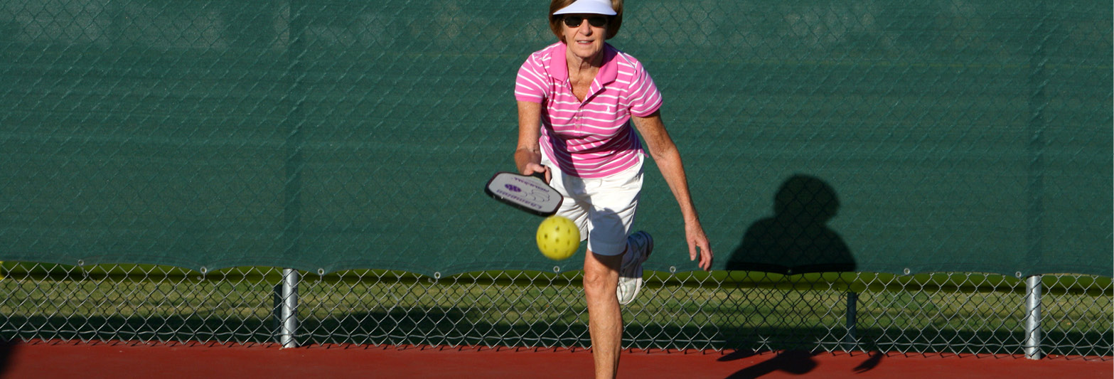 older woman playing pickleball