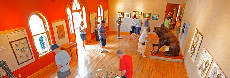 gallery at Station Arts Centre with patrons looking at art on walls and on display